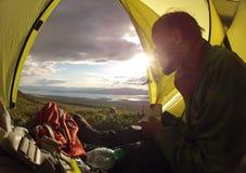 Reisender, der im Campingzelt sitzt Lizenzfreie Stockbilder