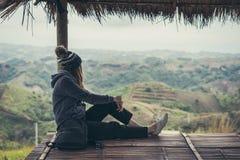 Reisender der jungen Frau, der Ansicht der Natur sitzt und schaut stockfotos