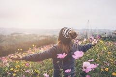 Reisender der jungen Frau, der auf dem Blumengebiet geht lizenzfreies stockbild