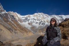 Reisender der jungen Frau, der vor Himalaja-Bergen sitzt Stockfotografie