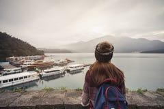 Reisender der jungen Frau, der eine schöne Ansicht Sonne-Mond-See betrachtet stockfotografie