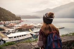 Reisender der jungen Frau, der eine sch?ne Ansicht Sonne-Mond-See betrachtet lizenzfreie stockfotos