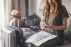 Reisender der jungen Frau, der intelligentes Telefon verwendet und Karte schaut stockfotos