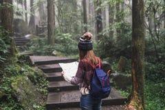 Reisender der jungen Frau, der Karte schaut und in das Natur educa geht lizenzfreie stockfotografie
