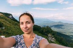 Reisender der jungen Frau macht selfie auf die Gebirgsoberseite am Sommertag Lizenzfreies Stockbild