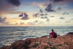 Reisender der jungen Frau sitzt auf dem Ufer des Winter Meeres und des wat stockfoto