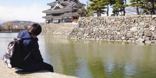 Reisender, der am See um das Teil des japanischen Schlosses sitzt Lizenzfreies Stockbild
