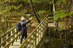 Reisender, der selfie mit Smartphone auf Holzbrücke im Wald nimmt stockfotografie