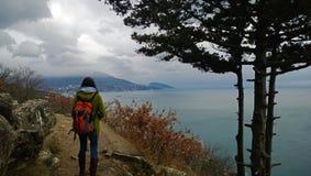 Reisender des jungen Mädchens mit dem Rucksack, der in den Abstand der schönen Ansicht des Meeres und der Klippen betrachtend ste Lizenzfreie Stockbilder