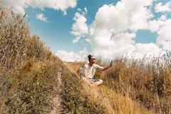 Reisender des jungen Mannes, der auf der Straße an der Landschaft sitzt und selfie mit Telefon macht Lizenzfreie Stockfotografie