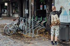 Reisender des jungen Mannes, der zum Stadtplan auf Straße schaut Lizenzfreies Stockfoto