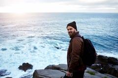 Reisender des jungen Mannes mit einem Rucksack auf seiner hinteren Stellung auf Felsen gegen schönes Meer mit Wellen und Sonnenun Stockfoto