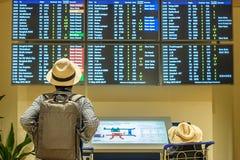 Reisender des jungen Mannes mit Hutpr?fungs-Flugzeit, asiatischer Passagier, der zum Informationsbrett im internationalen Flughaf lizenzfreies stockfoto