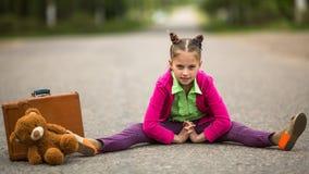 Reisender des kleinen Mädchens auf der Straße mit einem Koffer und einem Teddybären aTrvel Stockfoto