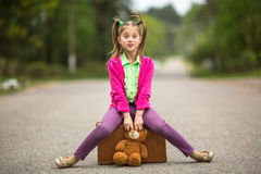 Reisender des kleinen Mädchens in der hellen Kleidung auf der Straße mit einem Koffer und einem Teddybären glücklich Stockfotos