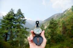 Reisender des Kompassses in der Hand in den Bergen Stockbild