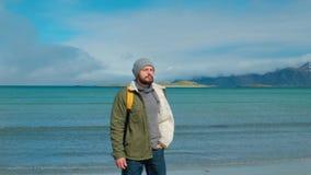 Reisender in einer grünen Jacke und in einem gelben Rucksack steht auf dem Strand und gegen den Hintergrund von hohen Bergspitzen stock video