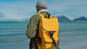 Reisender in einer grünen Jacke und in einem gelben Rucksack steht auf dem Strand und gegen den Hintergrund von hohen Bergspitzen stock footage