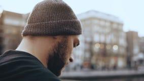 Reisender 4K, der mit Smartphone in Amsterdam geht Nahes hohes des Extrems Mann im Hut geht entlang alten Stadtflussdamm stock video