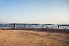 Reisender Mann mit Rucksackblicken auf Meer und Himmel stockfotos