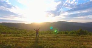 Reisender mit den angehobenen Händen grüßt Sonnenaufgang von hinten Berge gegen endlosen blauen Himmel stock video footage
