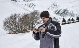 Reisender mit einem Smartphone in den Bergen lizenzfreie stockbilder