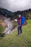 Reisender mit Karte auf Ufer von einem Gebirgsfluss Lizenzfreie Stockfotografie