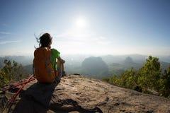 Reisender mit Rucksack sitzen auf dem Bergspitzefelsen, Stelle beobachtend stockfoto
