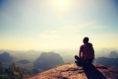 Reisender mit Rucksack sitzen auf dem Bergspitzefelsen, Stelle beobachtend lizenzfreie stockbilder