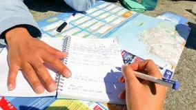 Reisender schreibt Anmerkungen auf ein Notizbuch über den Reiseplan stockfotografie