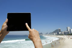 Reisender Tourist, der Tablet bei Rio de Janeiro Brazil Beach verwendet Stockbilder