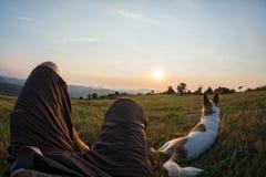 Reisender und sein Hund, die im Gras sitzen und das sunse aufpassen Lizenzfreie Stockfotos