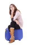 Reisendes Konzept: Frau, die auf ihrem Koffer sitzt Stockfoto