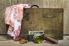 Reisendes Konzept von Retro- besteht Koffer, Kamera, Sonnenbrille, Mundorgan, Schal und auf hölzernem Hintergrund Stockfotos