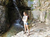 Reisendes Mädchen nahe dem Wasserfall lizenzfreie stockfotografie