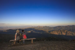 Reisendes Mann- und Frauentrekking zur Spitze des Berges und der Entspannung Stockfotos