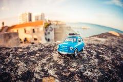 Reisendes Miniaturauto mit Gepäck auf einem Dach Stockfoto