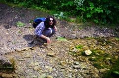 Reisendes Trinkwasser der Frau von einem Nebenfluss stockbilder
