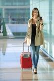 Reisendfrau, die ein intelligentes Telefon in einem Flughafen geht und verwendet Lizenzfreie Stockfotografie
