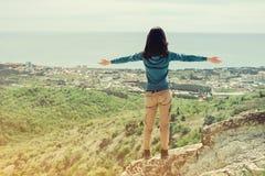 Reisendfrau, die mit den angehobenen Armen auf Spitze des Felsens steht Stockfotos