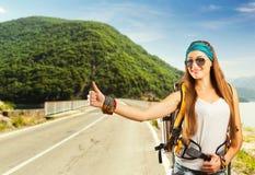 Reisendfrau fängt ein Auto Stockfoto