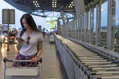 Reisendfrau im Flughafenabfertigungsgebäude unter Verwendung des mobilen Smartphone mit Gepäck und Tasche auf Flughafenlaufkatzen stockbilder