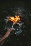 Reisendhand, die Tasse Kaffee über dem Lagerfeuer hält Stockfotografie