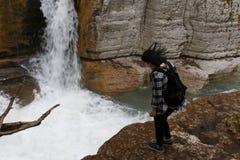 Reisendmädchen, das in Wasserfallschlucht geht Wanderermädchen mit dem Rucksack, der nahes Wasser des Wasserfalls steht Lizenzfreie Stockfotografie