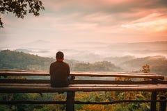 Reisendmann, der in den Bergen mit drastischem Himmel Sonnenaufgang nebelig betrachtet lizenzfreies stockbild
