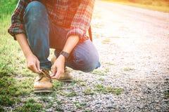Reisendmann-Hand-` s, das Schnürsenkel auf Straße Reisendem und holi bindet Stockfoto