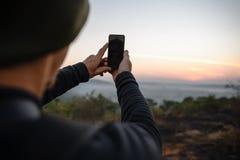 Reisendnehmen Schüsse telefonisch bei Sonnenaufgang Lizenzfreie Stockfotografie