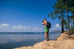 Reisendphotograph mit dem Rucksack, der Fotos des Sommers auf Strand von hinten macht Stockfoto