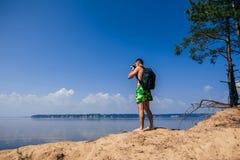 Reisendphotograph mit dem Rucksack, der Fotos des Sommers in Fluss unter einen blauen sauberen Himmel auf Strand macht Lizenzfreie Stockbilder