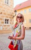 Reisendstände der jungen Frau in Prag ist eine gemütliche alte Straße Stockfoto